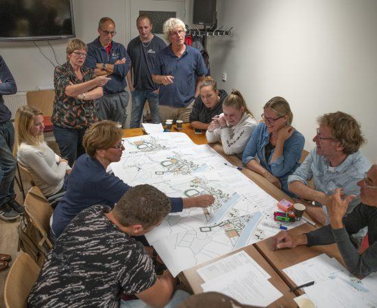 Inwoners van Woltersum zitten met een grote groep aan tafel, om een plattegrond van Woltersum heen, en praten over de dorpsvernieuwing van Woltersum.