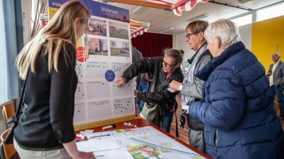 Inwoners staan bij een kraampje waar een mevrouw uitlegt wat haar plannen zijn voor de dorpsvernieuwing in Woltersum.