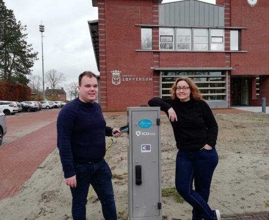 Joost en Louwina bij een laadpaal voor het gemeentehuis van Loppersum