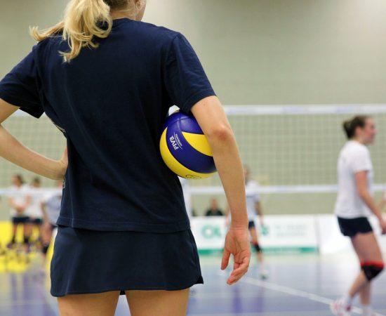 Vrouw op volleybalveld met een volleybal onder haar arm.