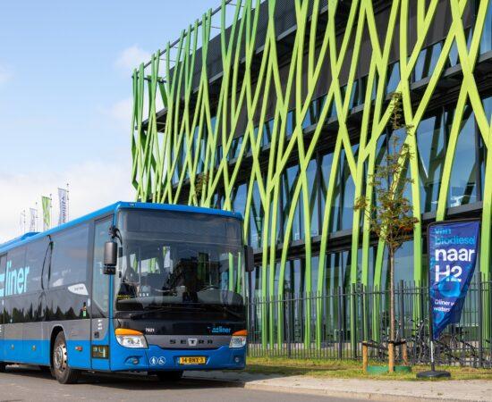 Decoratieve afbeelding van een bus die voor het Hive.Mobility gebouw langsrijdt