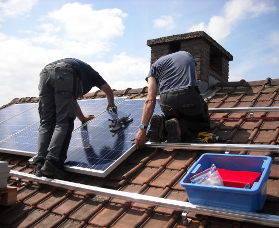 Sfeerbeeld van installateurs die zonnepanelen op een dak monteren.