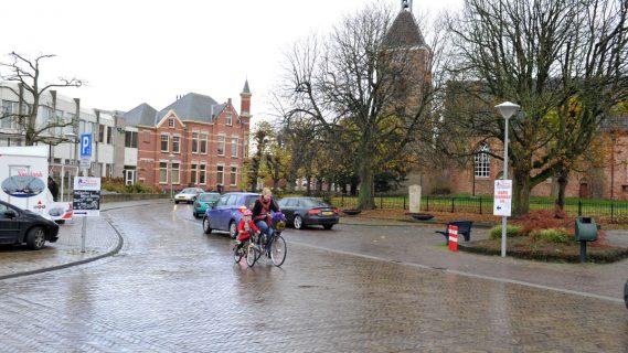Moeder fietst met kind langs de kerk in Uithuizen.