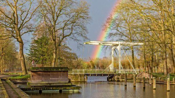 Sfeerbeeld van een bruggetje met regenboog op de achtergrond in Slochteren.
