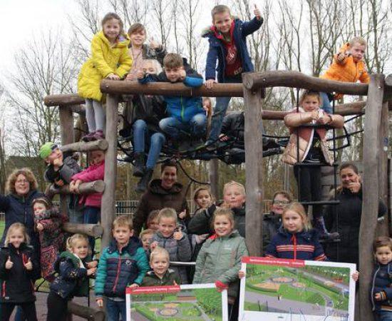 Kinderen in een speeltoestel met bouwtekeningen in hun hand van de nieuwe speeltuin in Zoutkamp.