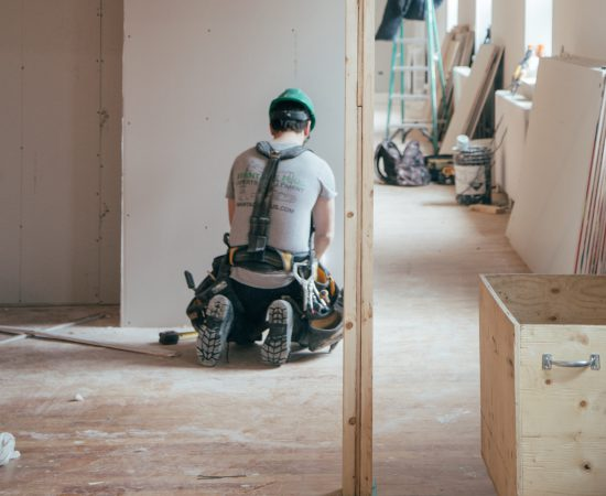 Bouwvakker werkt aan muren in een woning.