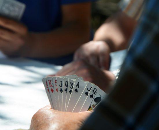 Mensen spelen een potje kaarten aan tafel, iets wat veel gebeurd in dorpshuizen.
