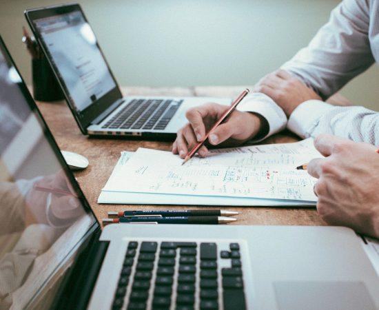 Sfeerbeeld van twee mannen die achter hun computer zitten en op papier iets samen bespreken.