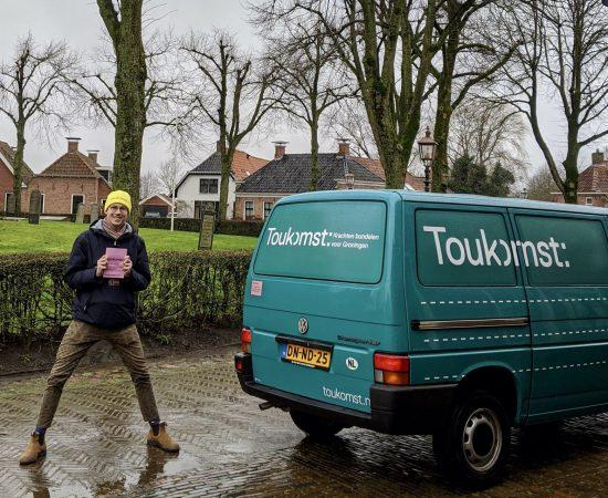 Toukomstcollega Thijs staat vrolijk bij de Toukomstbus met een Toukomstmuts op zijn hoofd.
