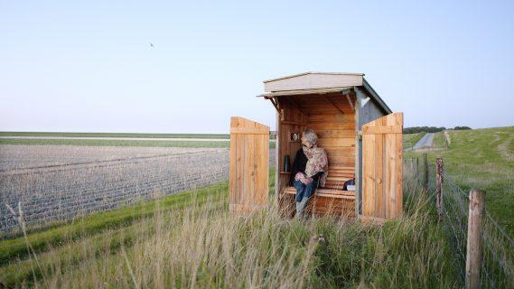 Vrouw in een klein houten hutje tussen lang uitgestrekte akkers.