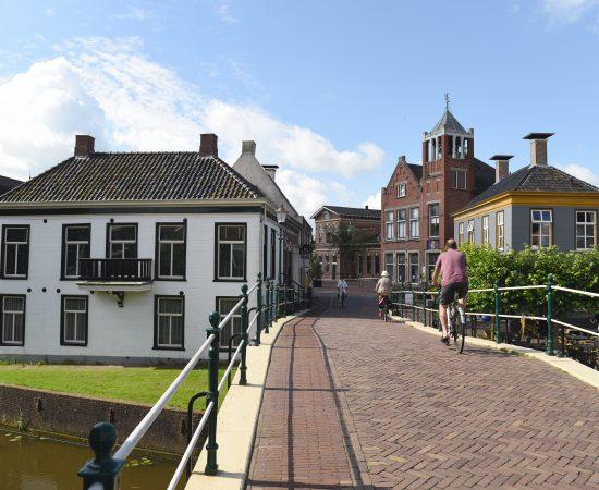 Fietsers over een bruggetje in Winsum, een dorp in de gemeente Het Hogeland.