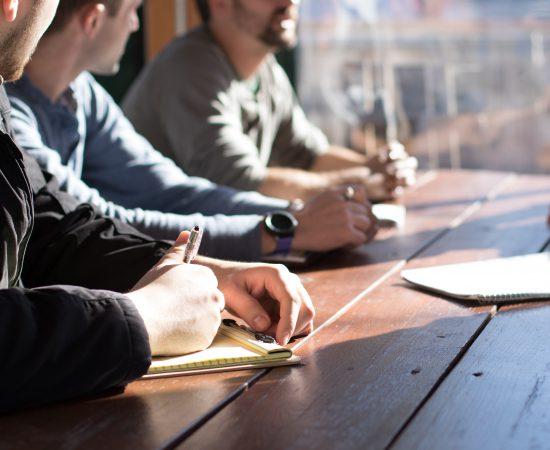 Sfeerbeeld van mensen aan tafel die tijdens een overleg opletten en dingen noteren.