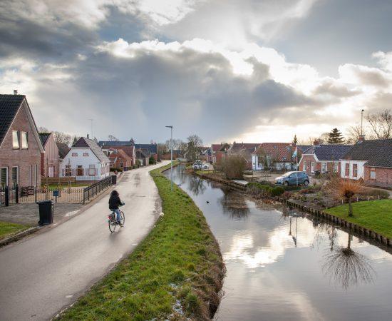 Vrouw fietst langs het kanaal in Woltersum.