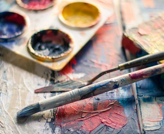 Sfeerbeeld van verfgerei, zoals kwasten en verf, op een doek.
