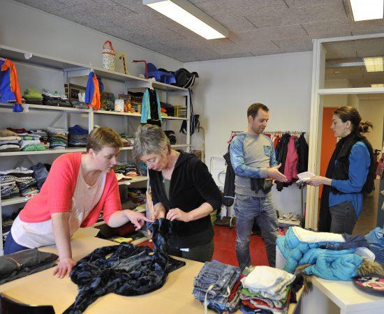 Sfeerbeeld van een bewonersinitiatief, mensen die kleding ruilen in de ruilwinkel het Heerdenhoes in Beijum.