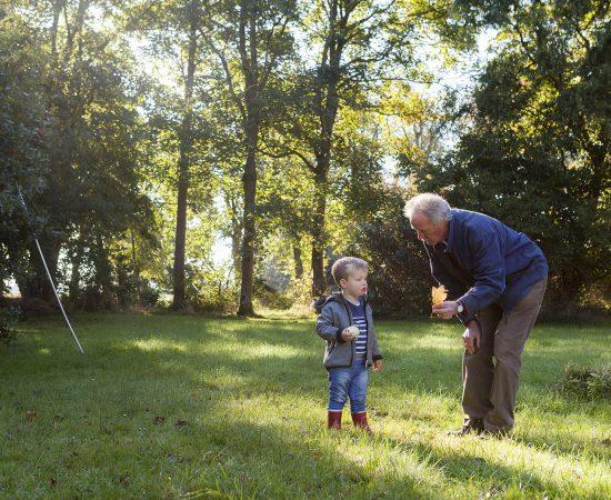 Sfeerbeeld van een opa met zijn kleinzoon die buiten aan het spelen zijn. De opa houdt een blaadje vast.