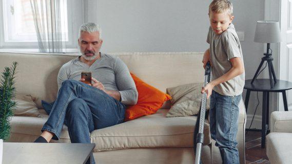 Sfeerbeeld van jongen die stofzuigt terwijl zijn vader op de bank naar zijn telefoon kijkt.