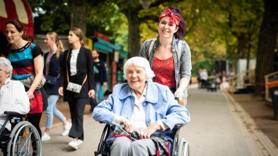 Sfeerbeeld van een jong meisje dat een oudere vrouw in een rolstoel duwt tijdens Noorderzon 2018 in Groningen.