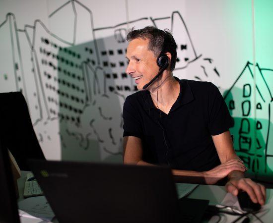 Gespreksleider Maarten Soppen zit achter zijn computer en is aan het bellen tijdens de bundelsessie van Toukomst