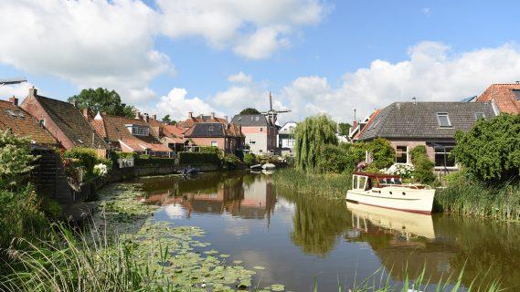 Sfeerbeeld voor het thematisch programma van een plaats in de provincie (Winsum) met huizen aan het water en bootjes in het water