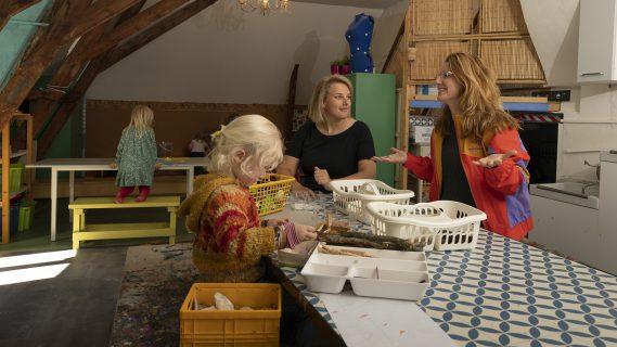 Twee volwassenen knutselen met een klein meisje aan tafel