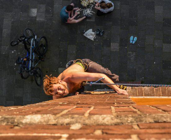 Collega Joren van Veen beklimt de muur van zijn eigen huis
