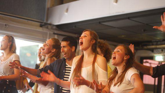 Sfeerbeeld van een koor dat uitbundig zingt.