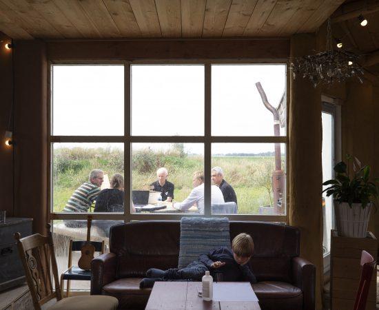 Binnenhuis ligt een kind op bank met op de achtergrond door het raam zichtbare buitenoverleg met vijf personen