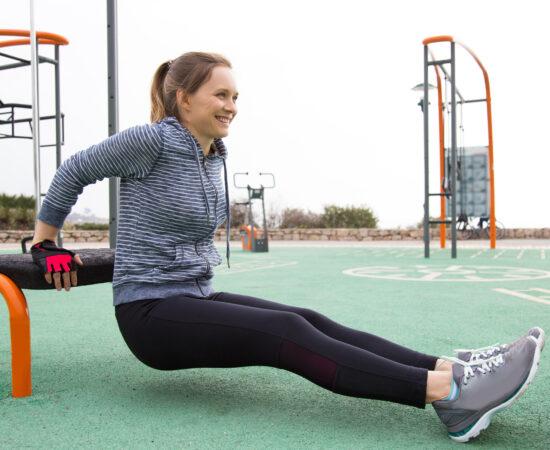 Meisje doet de oefening genaamd Dips in een beweegpark