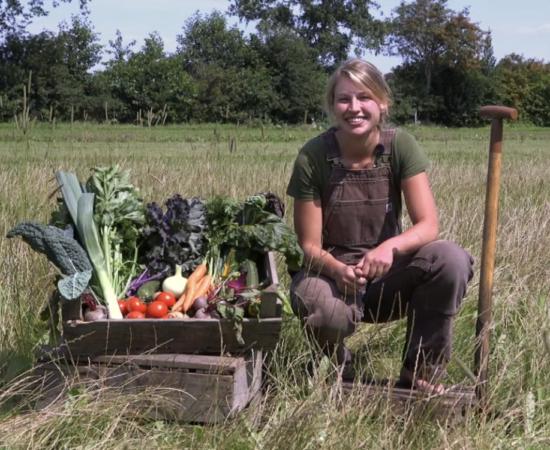 De drijfveer achter Tuinderij Het Groeipunt, Esther Kuiper, zit gehurkt naast een kratje met groenten.