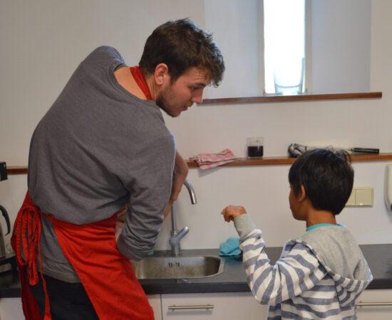 Decoratieve afbeelding van een man die een kind aan het helpen is in de keuken