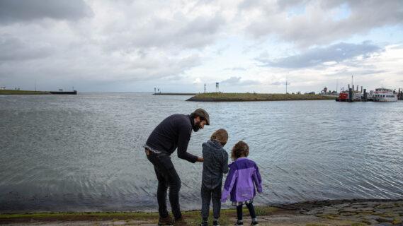 Decoratieve afbeelding van een vader met twee kinderen bij het water in Lauwersoog