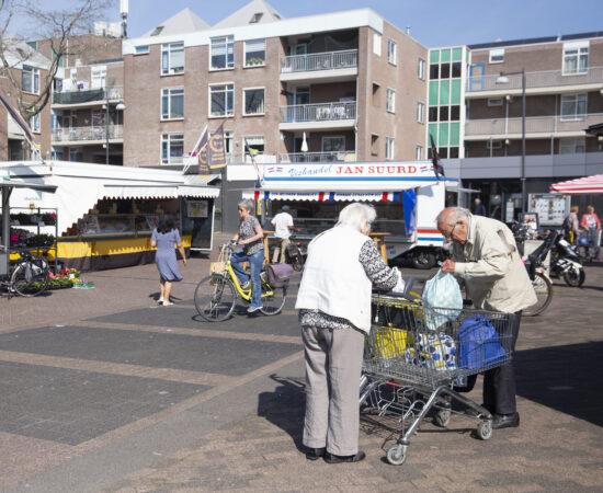 Decoratieve afbeelding van de markt waarop een ouder stel hun boodschappen in tasjes stopt