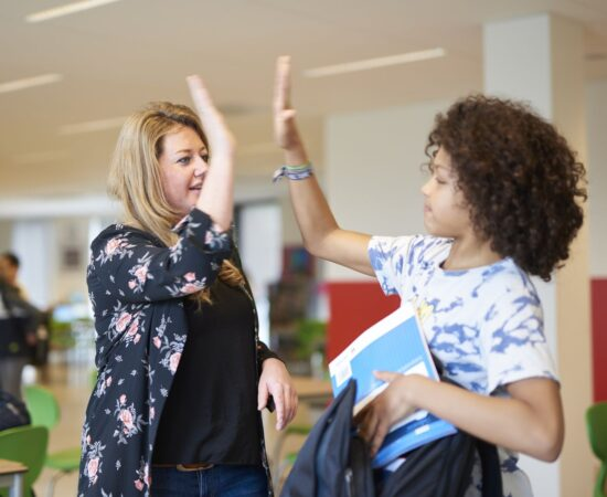 Decoratieve foto van een juf die een leerling een high five geeft op school