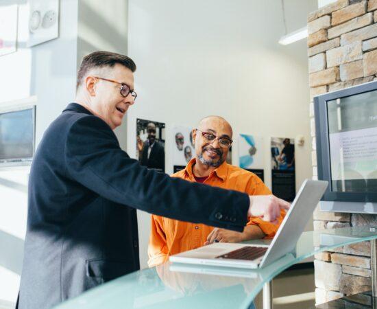 Decoratieve afbeelding van een leidinggevende die een werknemer iets laat zien op een computer