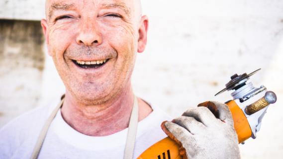 Decoratieve afbeelding van een lachende man met een slijptol in zijn handen