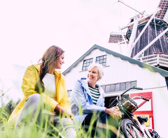 Decoratieve afbeelding van twee vrouwen met hun fiets voor een molen