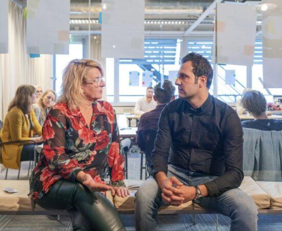 Decoratieve afbeelding van een man en een vrouw die samen op een bankje iets aan het overleggen zijn