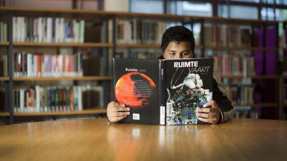 Decoratieve foto van een jongen die in de bibliotheek een boek leest