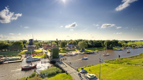 Sfeerbeeld voor het thematisch programma van de brug in Garnwerd die openstaat(Winsum) met huizen aan het water en bootjes in het water