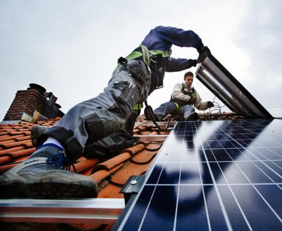 Decoratieve afbeelding van twee mannen bezig zijn met zonnepanelen op een dak te leggen.