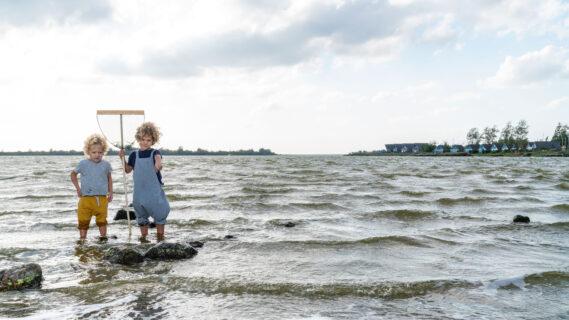 Decoratieve afbeelding van twee kinderen die met een visnetje in het Lauwersmeer staan