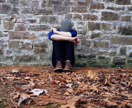 Decoratieve afbeelding van een jongen dat met zijn hoofd in zijn armen tegen een muur zit