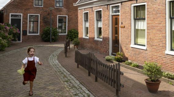 Decoratieve afbeelding van een klein meisje die door de straten van Winsum rent