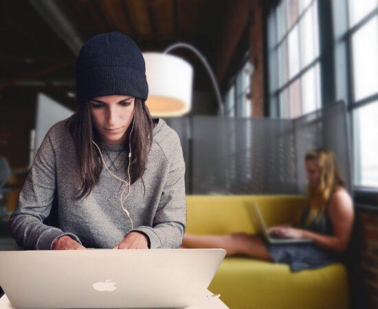 Decoratieve afbeeldingen van twee jonge vrouwen die aan het studeren zijn achter hun laptop