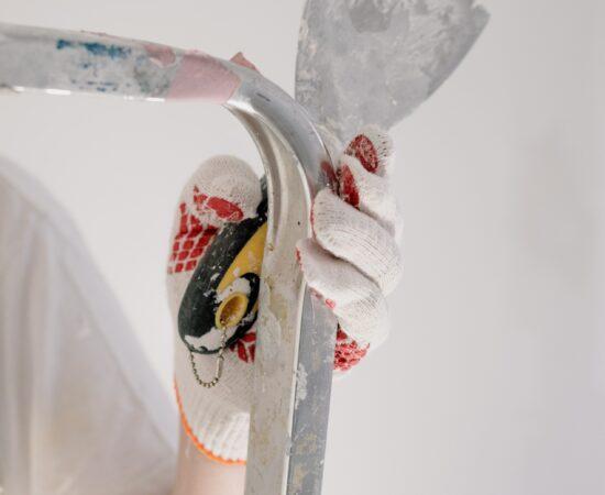 Decoratieve afbeelding van iemand op een lader met een spateltje in de hand om de muur te gaan stucen