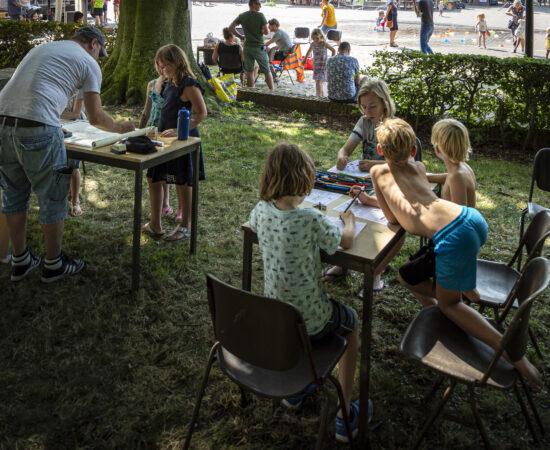 Kinderen tekenen aan schoolbankjes buiten