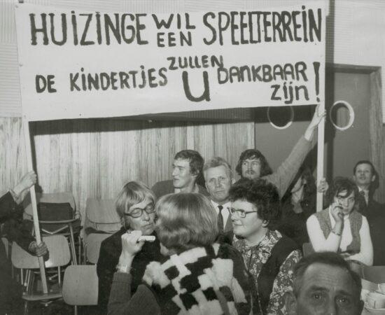 Decoratieve foto uit 1974 waarin bewoners oproepen tot een nieuw speelterrein voor de kinderen met een spandoek