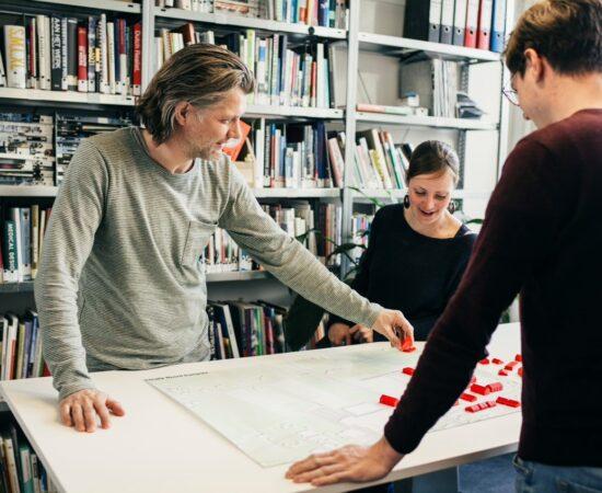 Decoratieve foto van intitatiefnemers van Roemte! om een tekentafel met plastic rode huisjes