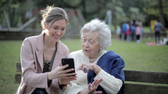 Decoratieve foto van een bejaarde vrouw en een vrouw van middelbare leeftijd die samen op een bankje naar een telefoon kijken